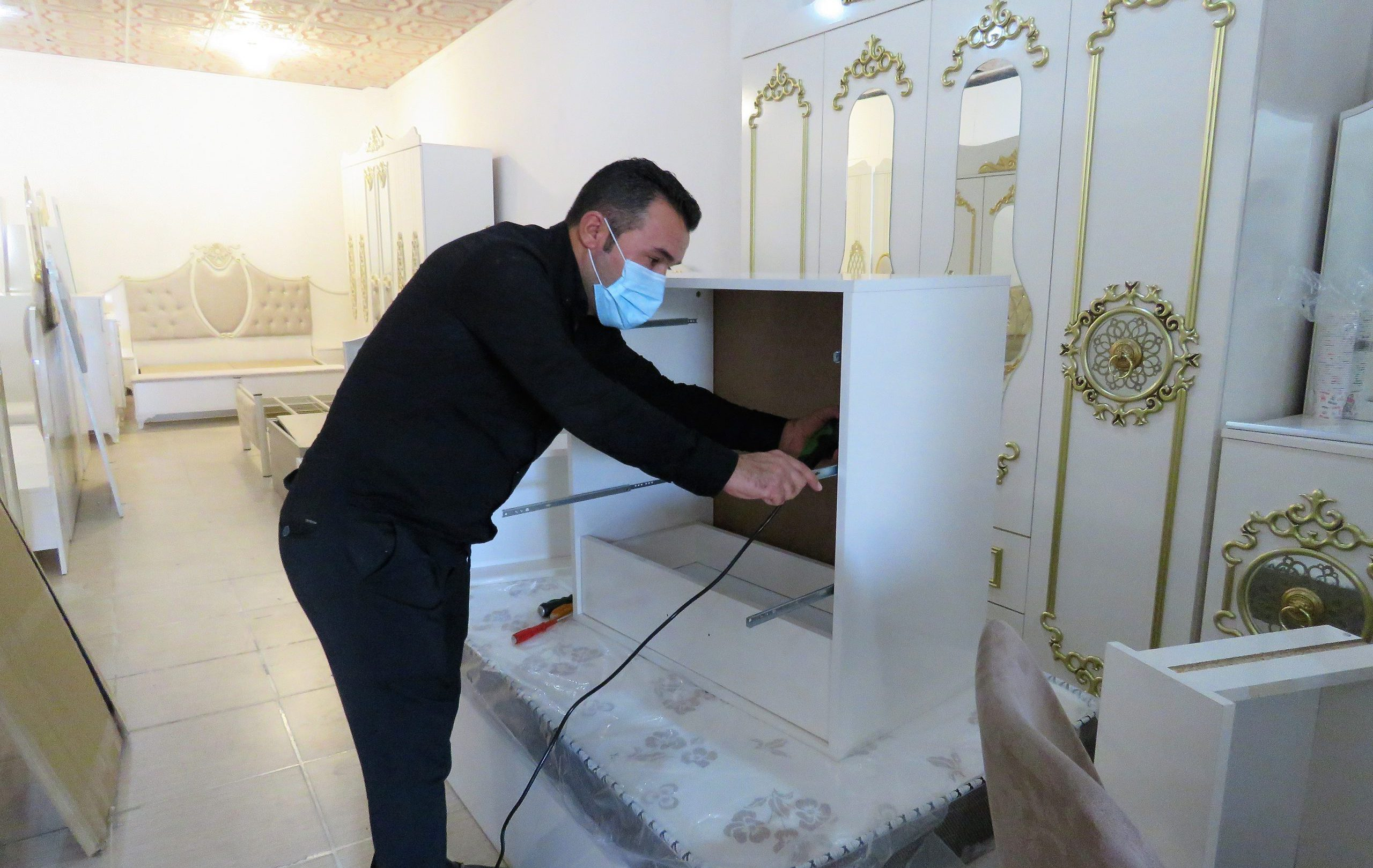 Beneficiary fixing a shelf in his furniture shop.