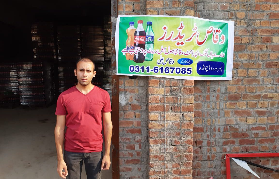 A beneficiary in front of a banner advertising soft drinks. Pakistan.