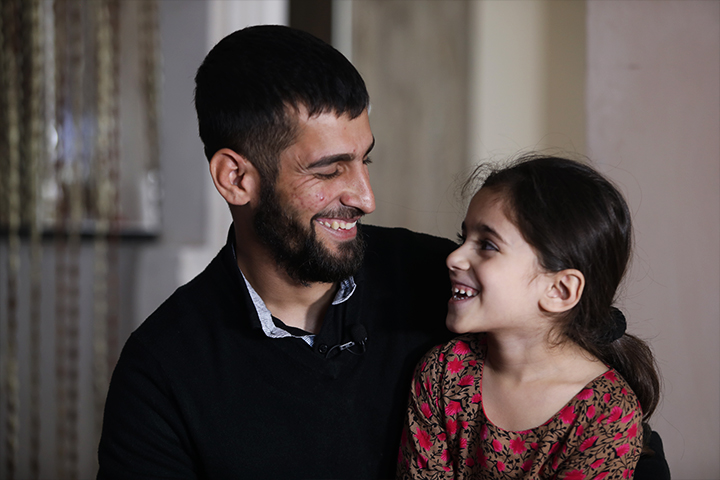 A man smiling at a little girl.
