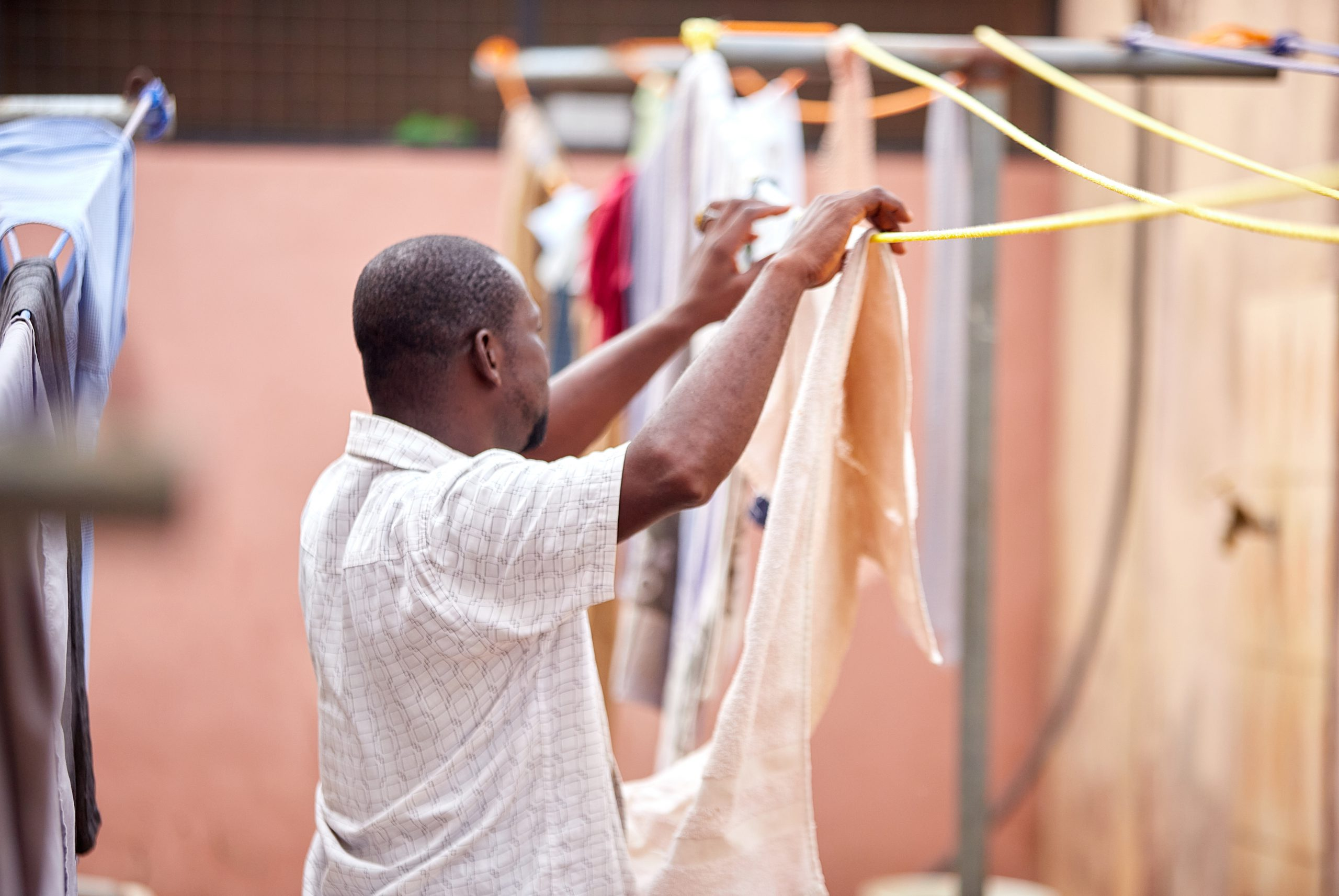 A Ghanaian man hanging clothes on a laundry line.