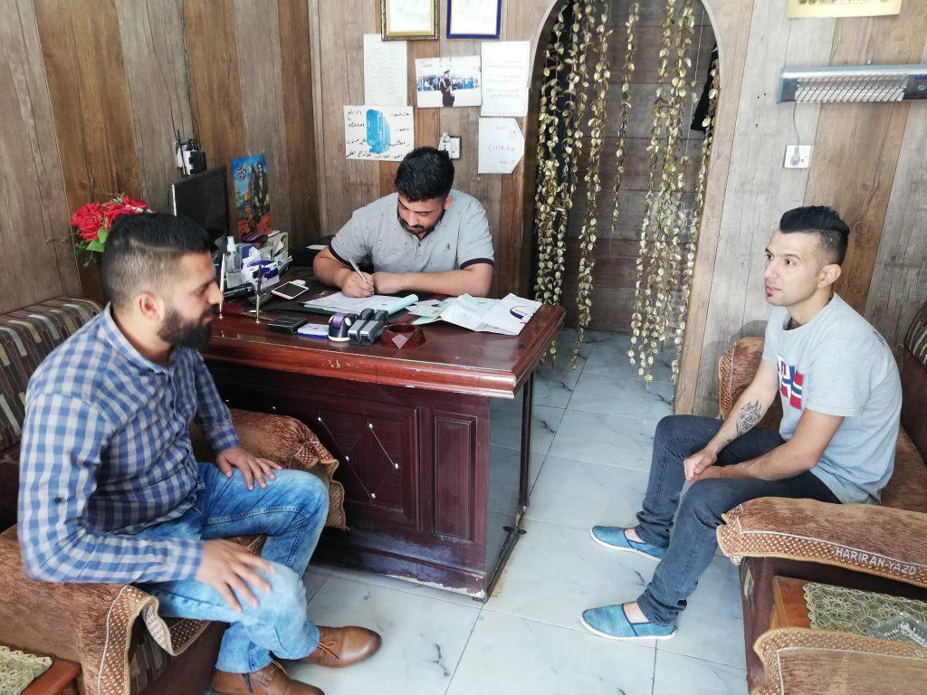 Men sitting around a desk in Baghdad.
