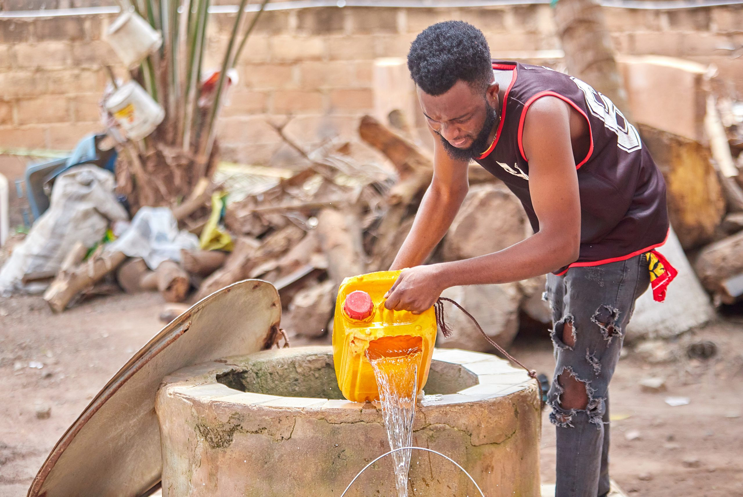 A Ghanaian man taking water from the well.