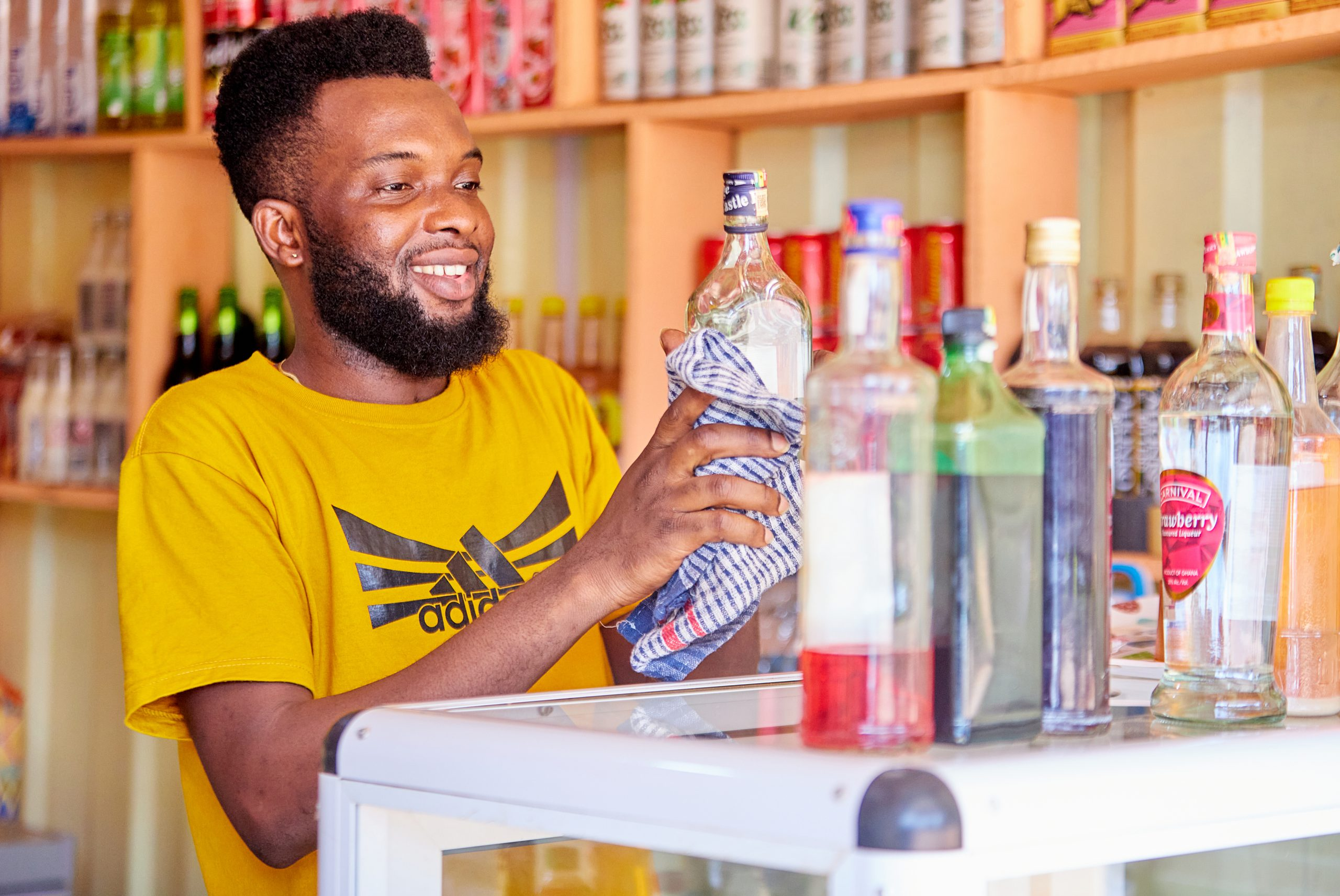 A Ghanaian man holding a glass bottle in his pub.