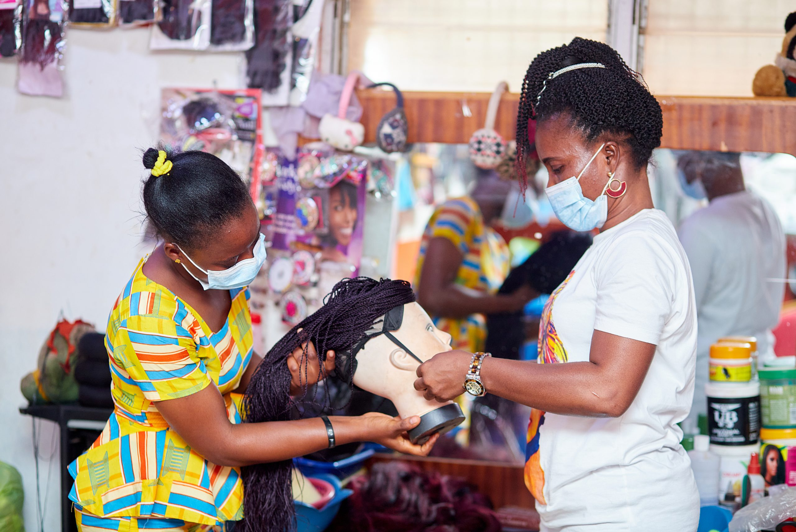 Two Ghanaian women making wigs.