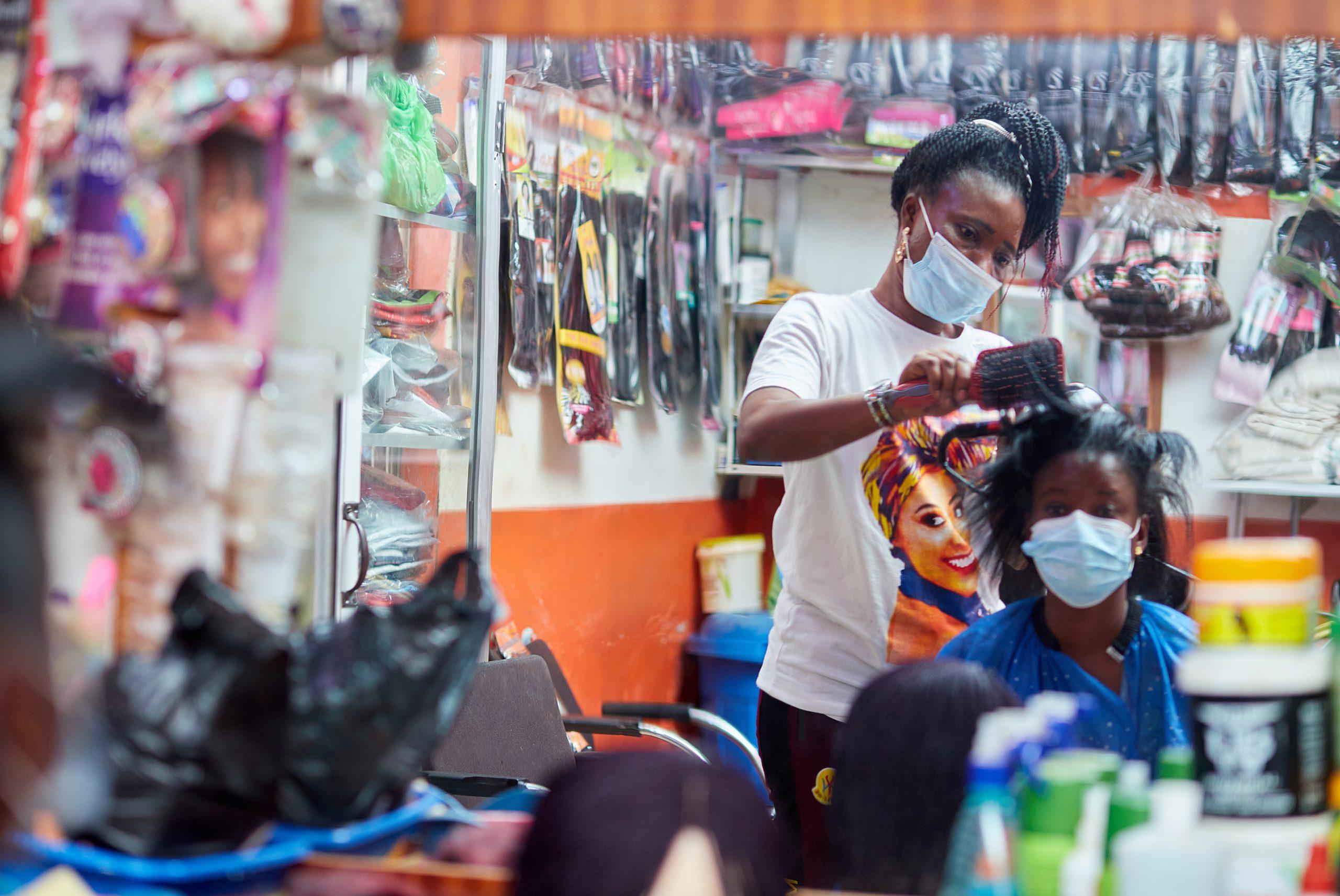 A Ghanaian hairdresser and her customer.
