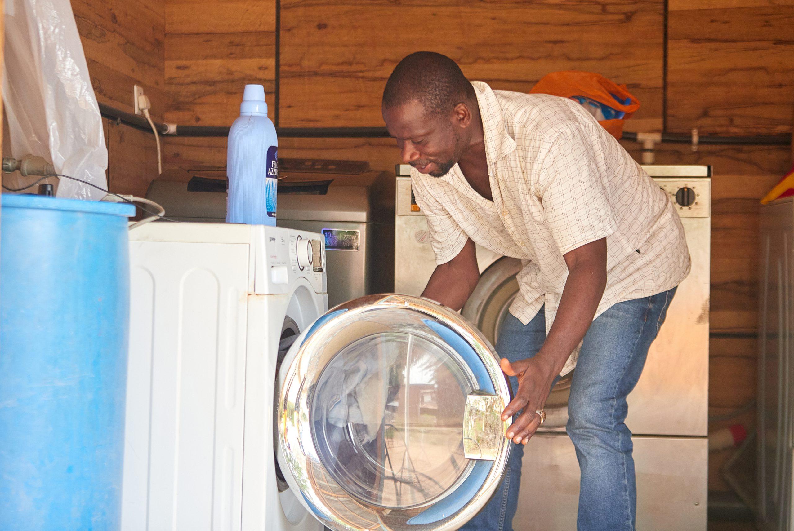 A Ghanaian man loading a washing machine.