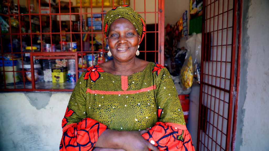 A Senegalese woman standing and smiling in front of her store.